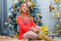 在家打开礼物的欢乐的小女孩 免版税库存照片