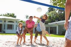 在家打排球的家庭在庭院里 免版税库存图片