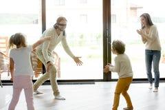 在家打滑稽的捉迷藏比赛的家庭孩子 免版税库存图片
