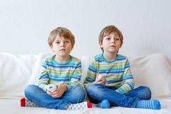 在家打电子游戏的两个小孩男孩 图库摄影