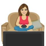 在家打电子游戏的少妇坐沙发 免版税库存图片
