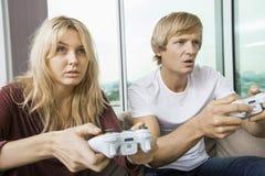 在家打电子游戏的年轻夫妇在客厅 免版税库存图片