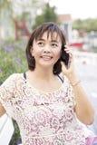 在家打电话在庭院里的亚裔妇女 库存图片