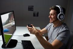 在家打计算机电子游戏的耳机的人 免版税库存照片