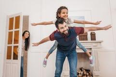 在家扛在肩上逗人喜爱的矮小的女儿的父亲 图库摄影