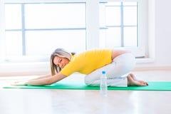 在家执行瑜伽执行的少妇 免版税库存照片