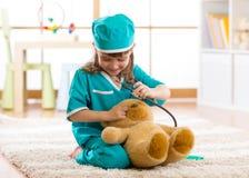 在家扮演有长毛绒玩具的逗人喜爱的孩子女孩医生 库存照片