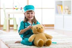 在家扮演有长毛绒玩具的逗人喜爱的孩子女孩医生 免版税图库摄影