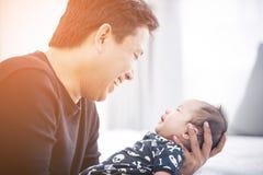 在家抱着他新出生的婴孩的骄傲的亚裔父亲 免版税图库摄影