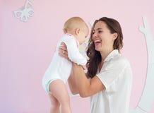 在家抱着逗人喜爱的婴孩的愉快的母亲画象 库存图片