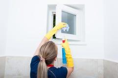 在家抹小窗口的少妇 免版税库存图片