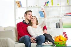 在家拍与电话的微笑的夫妇自画象照片 库存图片