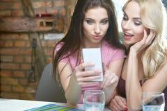 在家拍在电话的女孩照片 免版税库存图片