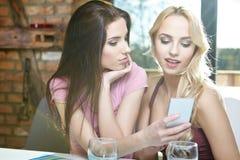 在家拍在电话的女孩照片 免版税图库摄影