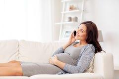 在家拜访智能手机的愉快的孕妇 图库摄影