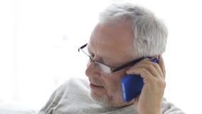 在家拜访智能手机24的愉快的老人 股票录像