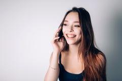 在家拜访电话的女孩 愉快的妇女使用一个智能手机 免版税库存照片