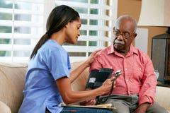 在家拜访高级男性患者的护士 库存照片