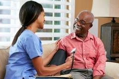 在家拜访高级男性患者的护士 免版税库存照片