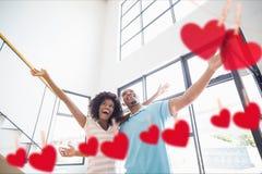 在家拥抱与垂悬的心脏的夫妇 免版税图库摄影
