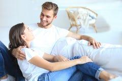 在家拥抱和享用在长沙发的愉快的年轻夫妇 图库摄影