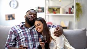 在家拥抱和放松用酒的甜mixed-race夫妇,悠闲时间 免版税库存图片