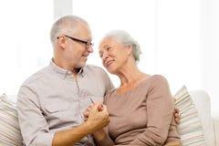在家拥抱在沙发的愉快的资深夫妇 免版税库存照片