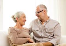 在家拥抱在沙发的愉快的资深夫妇 免版税图库摄影