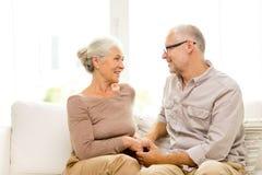在家拥抱在沙发的愉快的资深夫妇 图库摄影