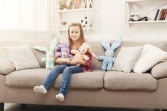在家拥抱她的在沙发的愉快的矮小的女孩玩具兔子 库存照片