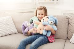 在家拥抱她的在沙发的愉快的矮小的女孩玩具兔子 库存图片