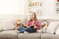 在家拥抱她的玩具熊和阅读书在沙发的愉快的矮小的女孩 免版税库存图片