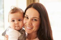 在家拥抱愉快的男婴的母亲 免版税库存照片