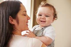 在家拥抱愉快的男婴的母亲 免版税库存图片