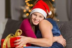 在家拥抱母亲的愉快的女孩在圣诞节期间 库存照片