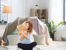 在家拥抱玩具熊的逗人喜爱的小女孩 免版税库存照片