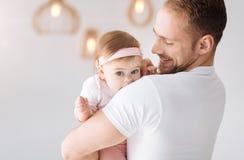 在家拥抱他的女儿的愉快的有胡子的父亲 免版税库存图片