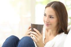 在家拿着咖啡杯的沉思女孩 免版税库存图片