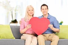 在家拿着大红色心脏的年轻夫妇 免版税库存照片