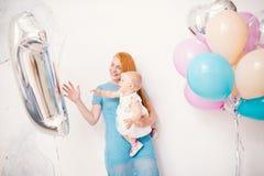 在家拿着女婴的年轻红发母亲在一件礼服的一年在白色背景 儿童` s holida的概念 免版税库存照片