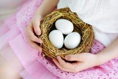 在家拿着巢用白色复活节彩蛋的逗人喜爱的小女孩在复活节天 免版税库存照片