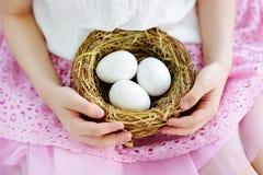 在家拿着巢用白色复活节彩蛋的逗人喜爱的小女孩在复活节天 库存照片