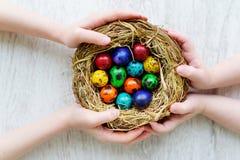 在家拿着巢用色的复活节彩蛋的两个孩子在复活节天 免版税库存照片