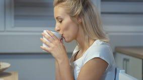 在家拿着杯子的快乐的少妇在厨房里 影视素材