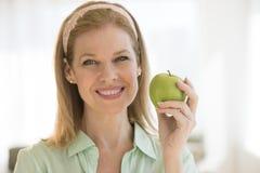 在家拿着格兰尼史密斯苹果苹果计算机的愉快的妇女 免版税库存图片