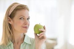 在家拿着格兰尼史密斯苹果苹果计算机的成熟妇女 库存照片
