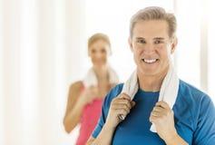 在家拿着毛巾的适合的成熟妇女在脖子上 免版税图库摄影