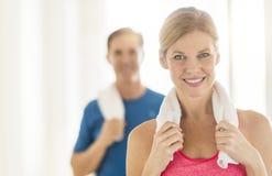 在家拿着毛巾的适合的成熟妇女在脖子上 图库摄影