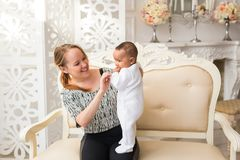 在家拿着混合的族种男婴的爱恋的母亲 免版税库存图片