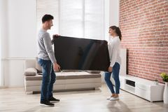在家拿着电视的夫妇 库存图片